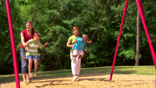 woman and teenage girl pushing children on a swing - この撮影のクリップをもっと見る 1278点の映像素材/bロール
