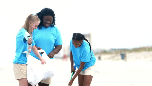 woman and teenage volunteers picking up litter on beach - 12 13 years stock videos & royalty-free footage