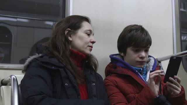 woman and teenager on the subway with mobile phone - handhaben stock-videos und b-roll-filmmaterial