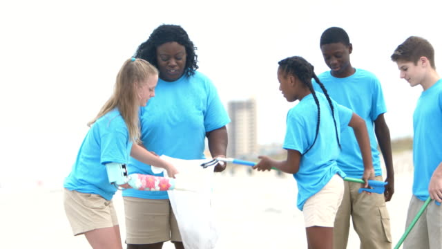 woman and teens volunteer to clean up beach - 12 13 years stock videos & royalty-free footage