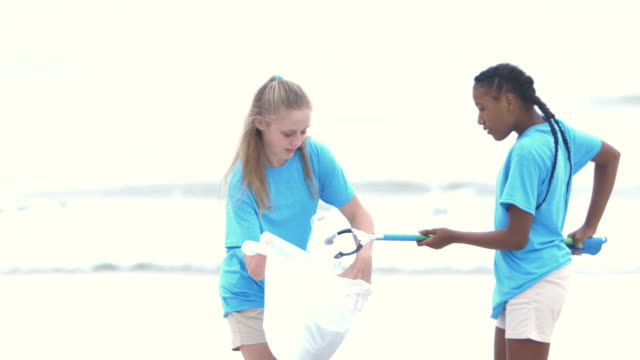 woman and teens volunteer to clean up beach - altruism stock videos & royalty-free footage