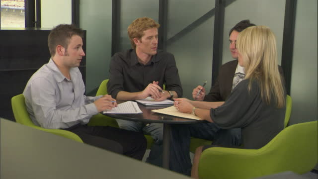ms pan woman and three men having business meeting at round table in office/ sydney, australia - round table discussion stock videos & royalty-free footage