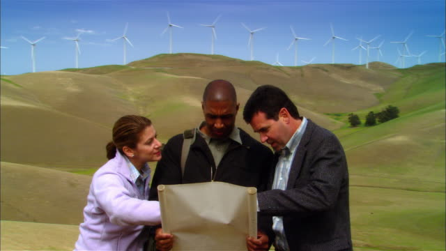 ms ds woman and two businessmen reading plans and surveying landscape near wind turbines on hill / livermore, california, usa - female with group of males stock videos & royalty-free footage