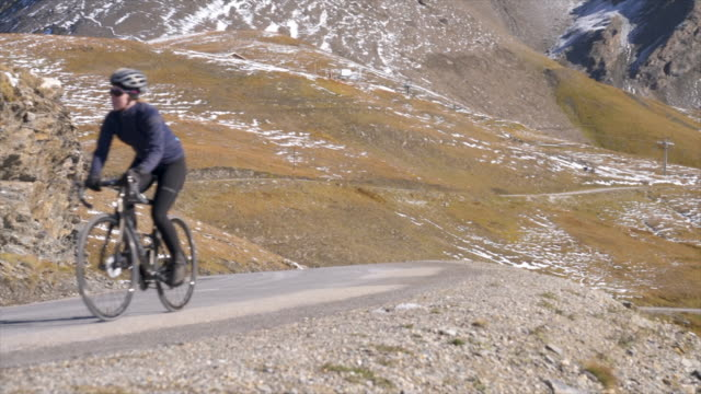 woman and two men cycling on bicycles, riding on road bikes in the winter. - uphill stock videos & royalty-free footage
