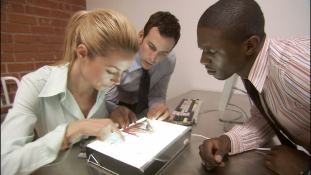 CU ZO MS Woman and two men looking at transparencies in lightbox, discussing project, and shaking hands in office / Los Angeles, California, USA