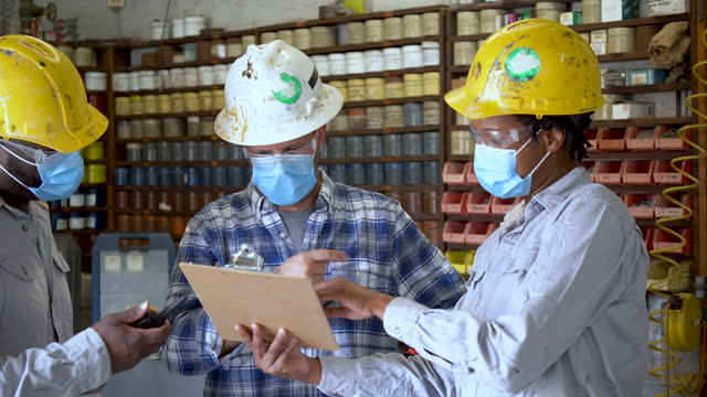 woman and two men working in factory wearing masks - clipboard stock videos & royalty-free footage