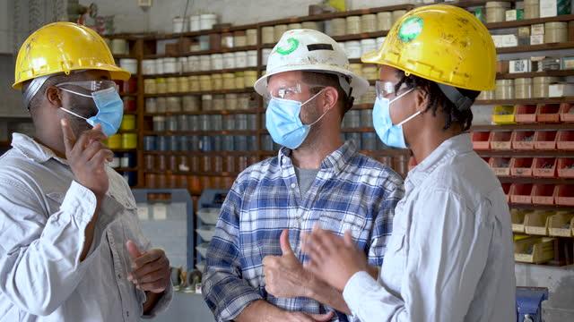 stockvideo's en b-roll-footage met vrouw en twee mensen die in fabriek werken die maskers dragen - drukker