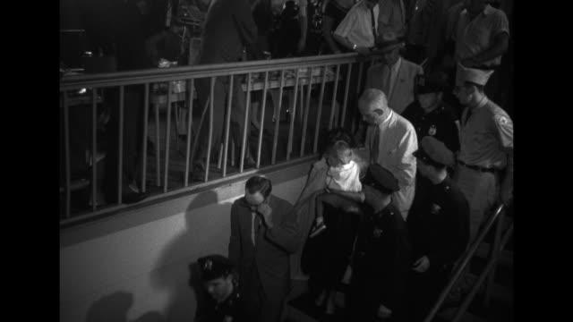 woman and young boy walk away from gangplank as ss andrea doria survivors begin to enter harbor building at new york harbor / little boy walks, with... - skådespelerska bildbanksvideor och videomaterial från bakom kulisserna