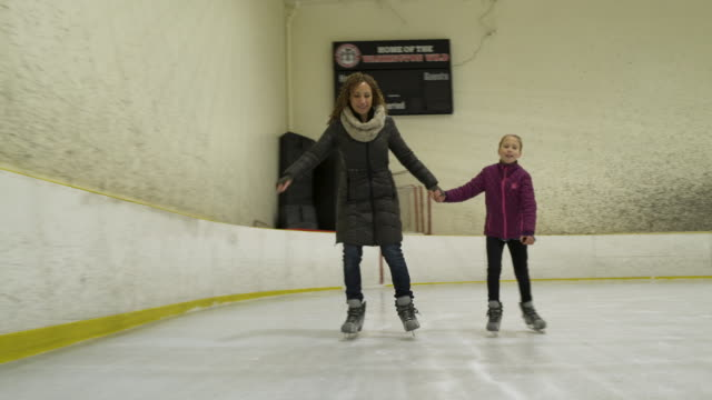 vidéos et rushes de woman and young girl ice skating together with girl tripping over. - trébucher