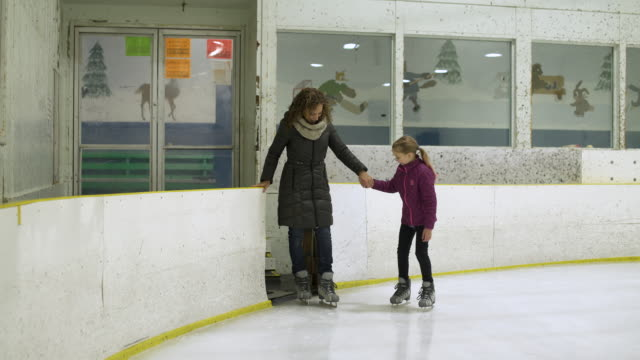 woman and young girl on ice rink ice skating together holding hands. - isrink bildbanksvideor och videomaterial från bakom kulisserna
