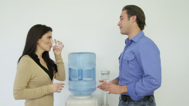 ms woman and young man having discussion standing next to a water cooler - office politics stock videos & royalty-free footage