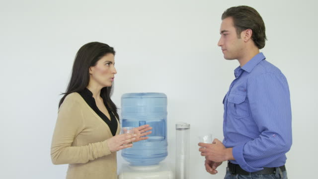 ms woman and young man having discussion standing next to a water cooler, mature man joins them and they continue their chat - office politics stock videos & royalty-free footage