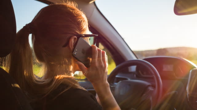 woman answering phone while driving - portability stock videos & royalty-free footage