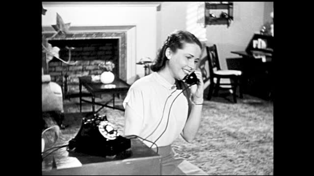 woman answers telephone in the living room while smiling, sits down to talk - 1940 1949 stock-videos und b-roll-filmmaterial