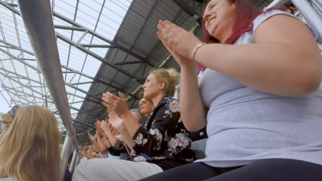 ld woman applauding sitting on the stadium tribune - enjoyment stock videos & royalty-free footage