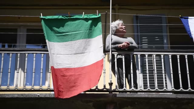a woman applauds and sings behind the italian flag during the flashmob during liberation day celebrations on april 25 2020 in turin italy italy's... - singing stock videos & royalty-free footage