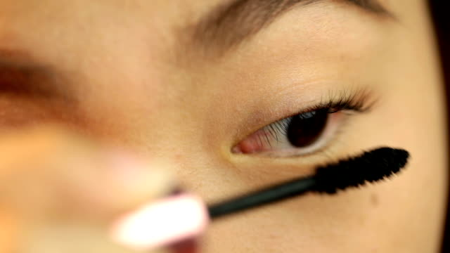 Woman applied mascara to her lashes