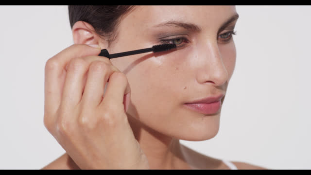 vidéos et rushes de woman applies black mascara to bottom lashes - mascara