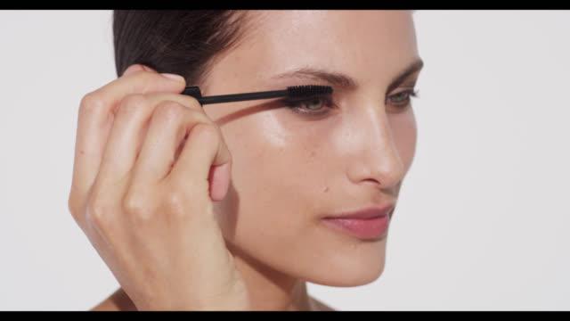 Woman applies black mascara to top lashes
