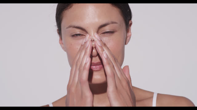 Woman applies cleanser to face with both hands