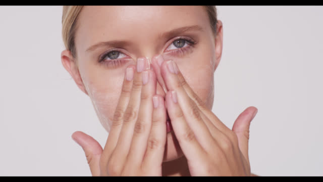 a woman applies cleanser to face with both hands - human skin stock videos & royalty-free footage