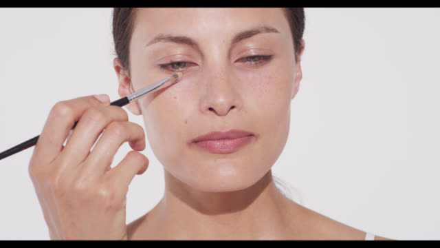 woman applies concealer with a brush under eye - urbanlip stock videos & royalty-free footage