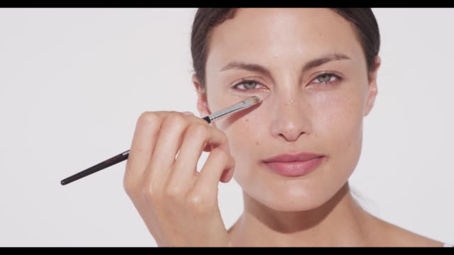 woman applies concealer with a brush under eye - メイクアップブラシ点の映像素材/bロール