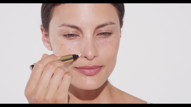 Woman applies concealer/highlighter pen either side of nostrils