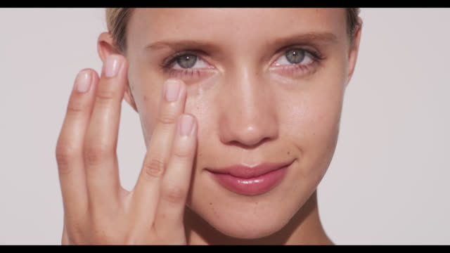 woman applies eye cream to lower lid of right eye - strofinare toccare video stock e b–roll