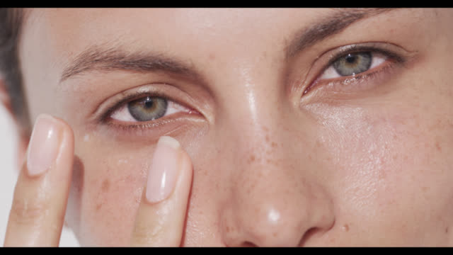 woman applies eye cream to under eye area - prendersi cura del corpo video stock e b–roll