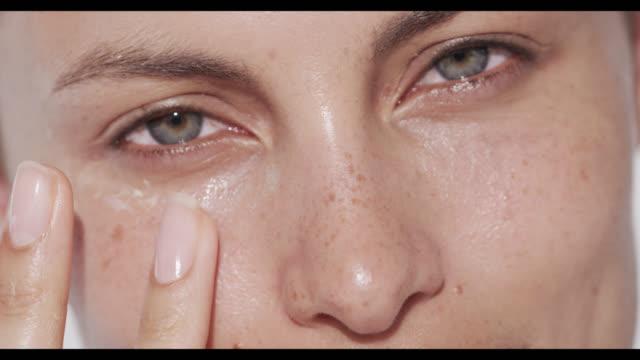 woman applies eye cream to under eye area - applying stock videos & royalty-free footage