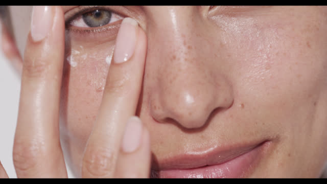 woman applies eye cream to under eye area - cream stock videos and b-roll footage