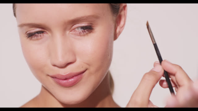 A woman applies eyebrow powder to left brow