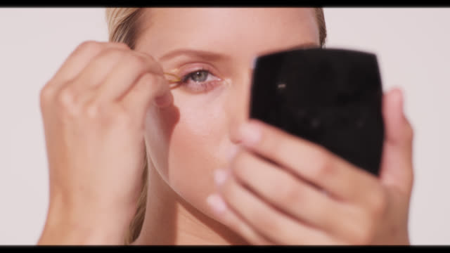 a woman applies eyelash inserts and smiles - wimper stock-videos und b-roll-filmmaterial