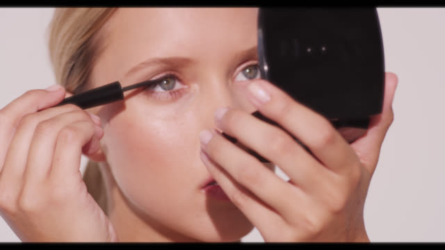 vídeos de stock, filmes e b-roll de a woman applies eyeliner to top eye  lid - delineador