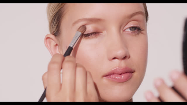 a woman applies eyeshadow with brush to right eye - urbanlip stock videos & royalty-free footage