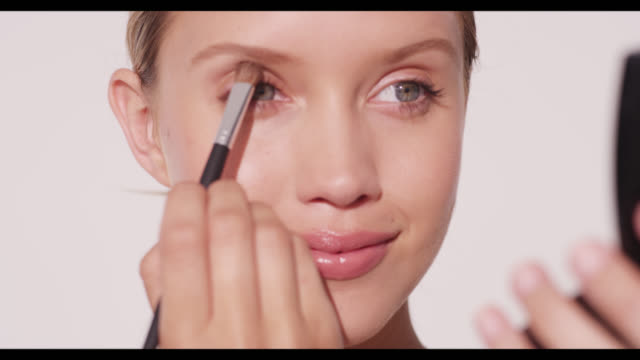A woman applies eyeshadow with brush to right eye