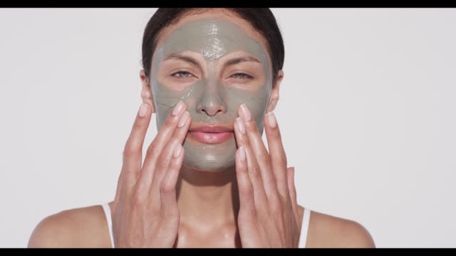 woman applies face mask with both hands - urbanlip stock videos & royalty-free footage