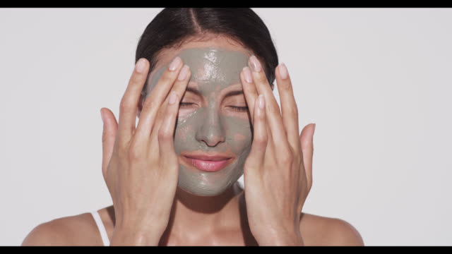 stockvideo's en b-roll-footage met woman applies face mask with both hands - lichaamsverzorging