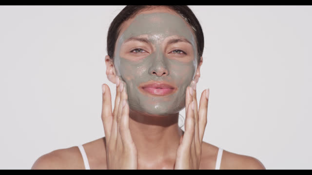 vídeos de stock e filmes b-roll de woman applies face mask with both hands - máscara facial