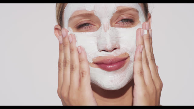 stockvideo's en b-roll-footage met woman applies face mask with hands and smiles - lichaamsverzorging