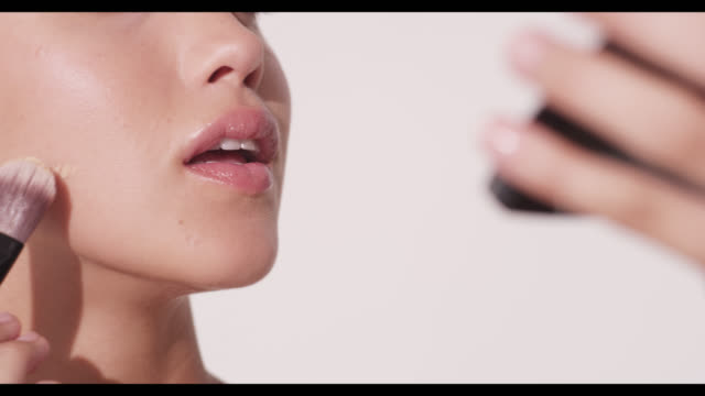 a woman applies foundation to cheek with brush - applying stock videos and b-roll footage