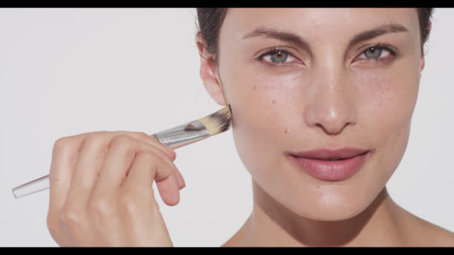 Woman applies foundation with brush to camera left side of face