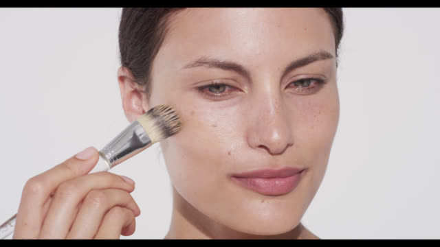 Woman applies foundation with brush to cheek