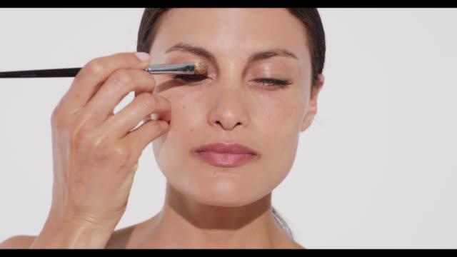 woman applies gold eyeshadow to camera left eyelid with brush - アイシャドウ点の映像素材/bロール