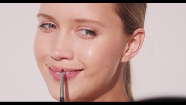 a woman applies lipgloss to lips and smiles - lipgloss stock-videos und b-roll-filmmaterial