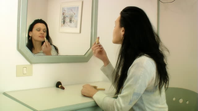 stockvideo's en b-roll-footage met woman applies lipstick in front of mirror - alleen oudere vrouwen