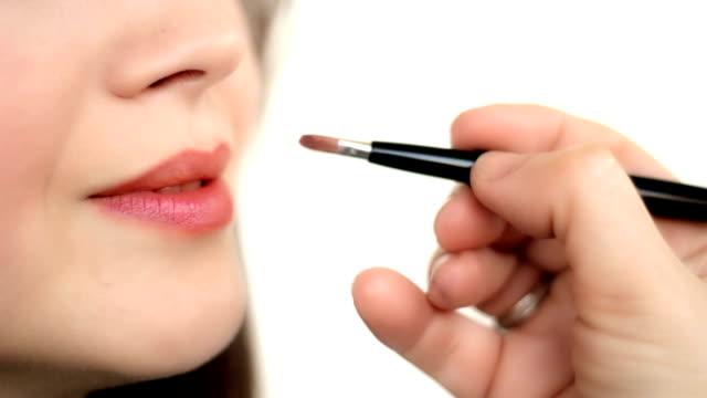 Woman applies lipstick