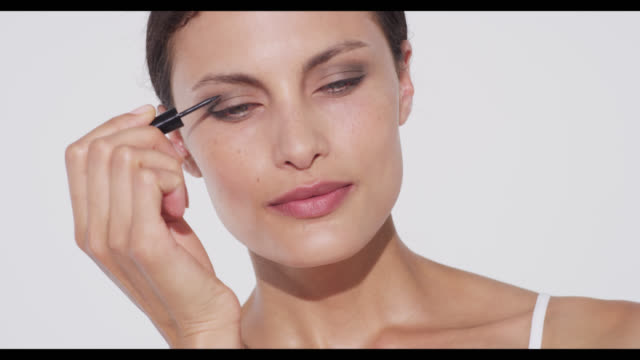 Woman applies liquid eyeliner to camera left eyelid while camera pans right