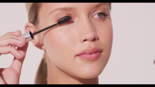 vidéos et rushes de a woman applies mascara to right eye - mascara